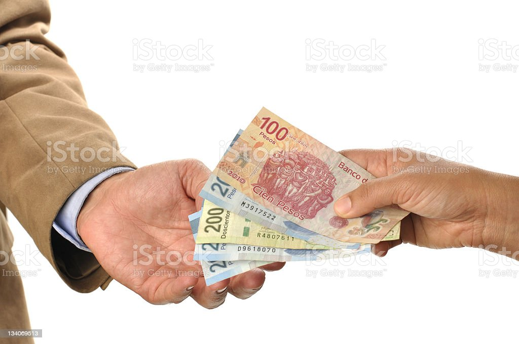 One hand giving foreign money to another hand stock photo