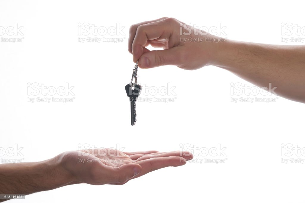 One hand giving key to another on isolated white background. stock photo