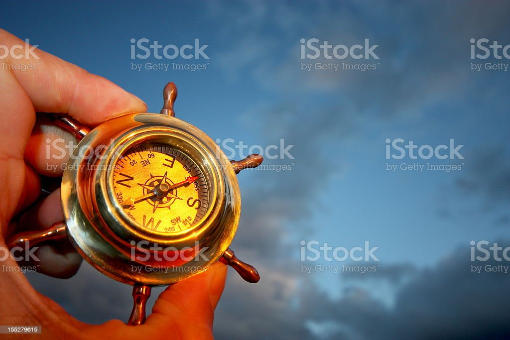 One hand holding a compass and a cloudy sky stock photo