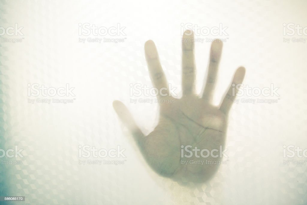 one hand  in back of glass stock photo