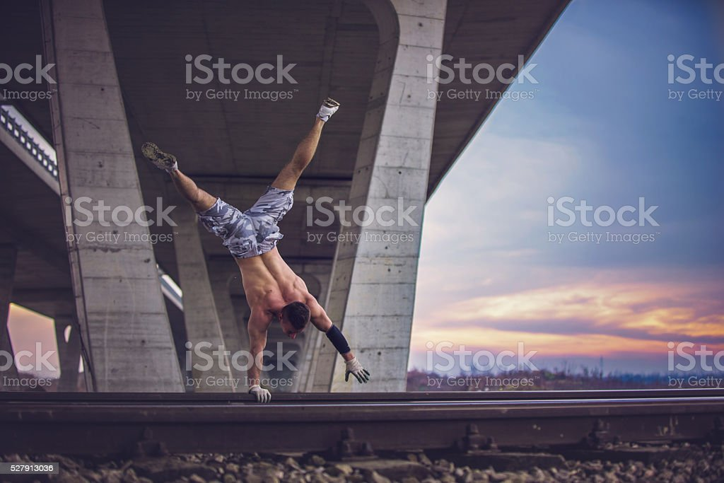 One hand stand on railroad tracks stock photo