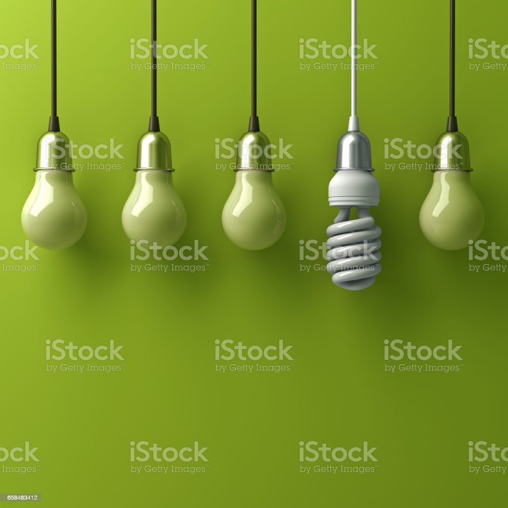 One hanging eco energy saving light bulb different and stand out from old incandescent lightbulbs with reflection on green background, individuality and different creative idea concept stock photo