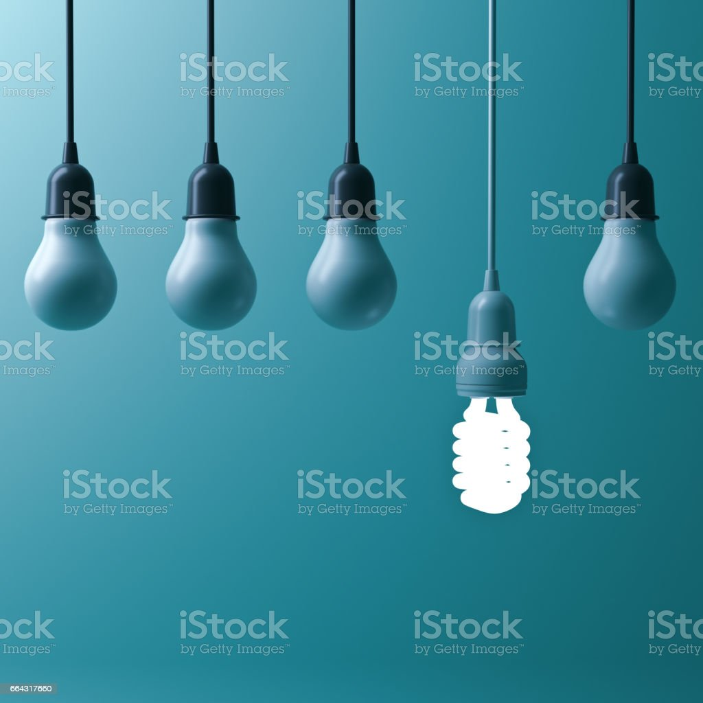 One hanging energy saving light bulb glowing different stand out from unlit incandescent bulbs with reflection on dark cyan background , leadership and different creative idea concept. 3D render stock photo