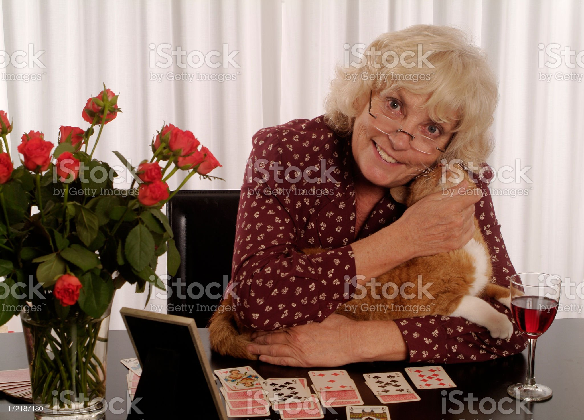 One happy senior woman playing cards cuddling cat royalty-free stock photo