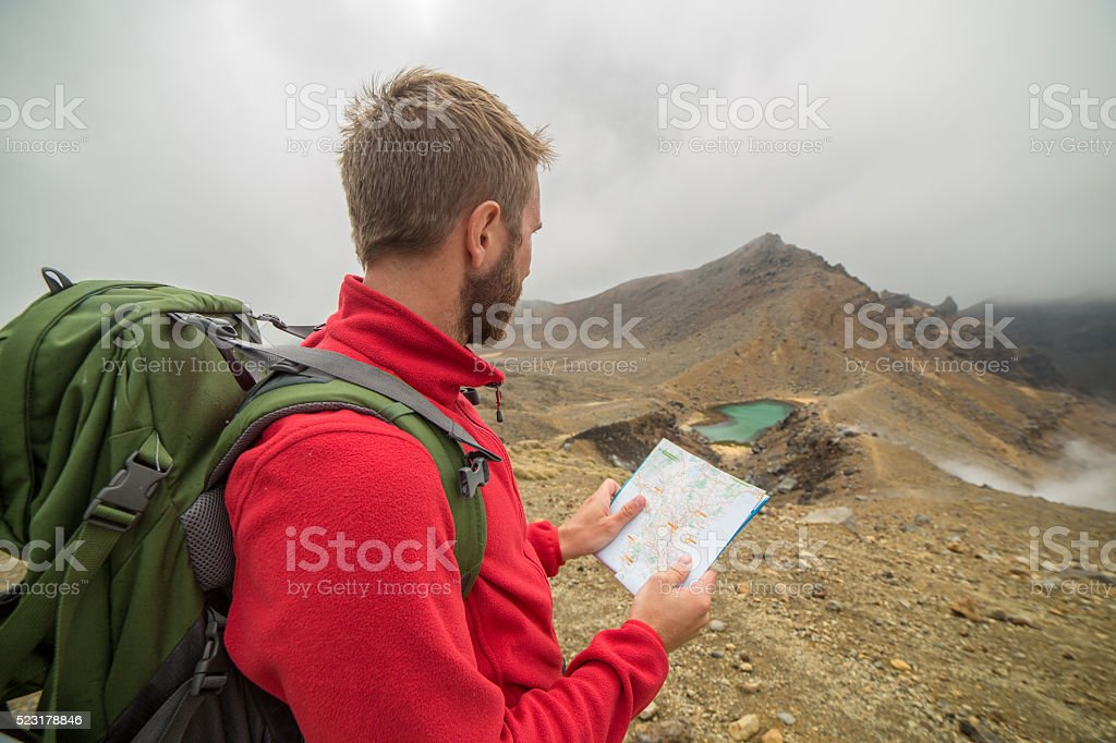 One hiker looks at map for directions-New Zealand stock photo