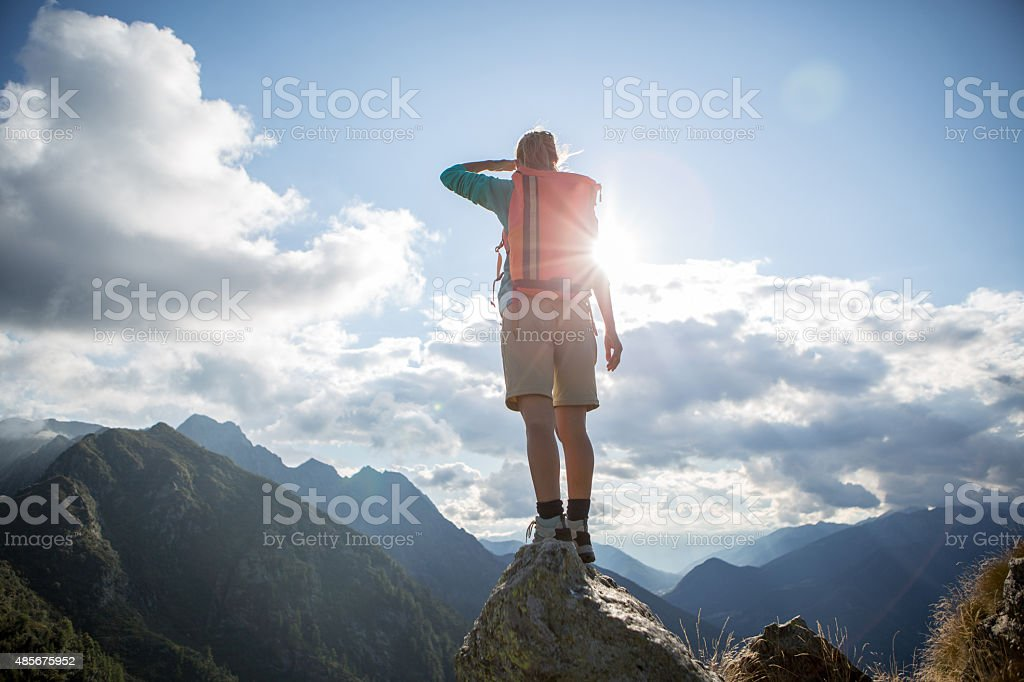 One hiker on mountain top looking at view stock photo