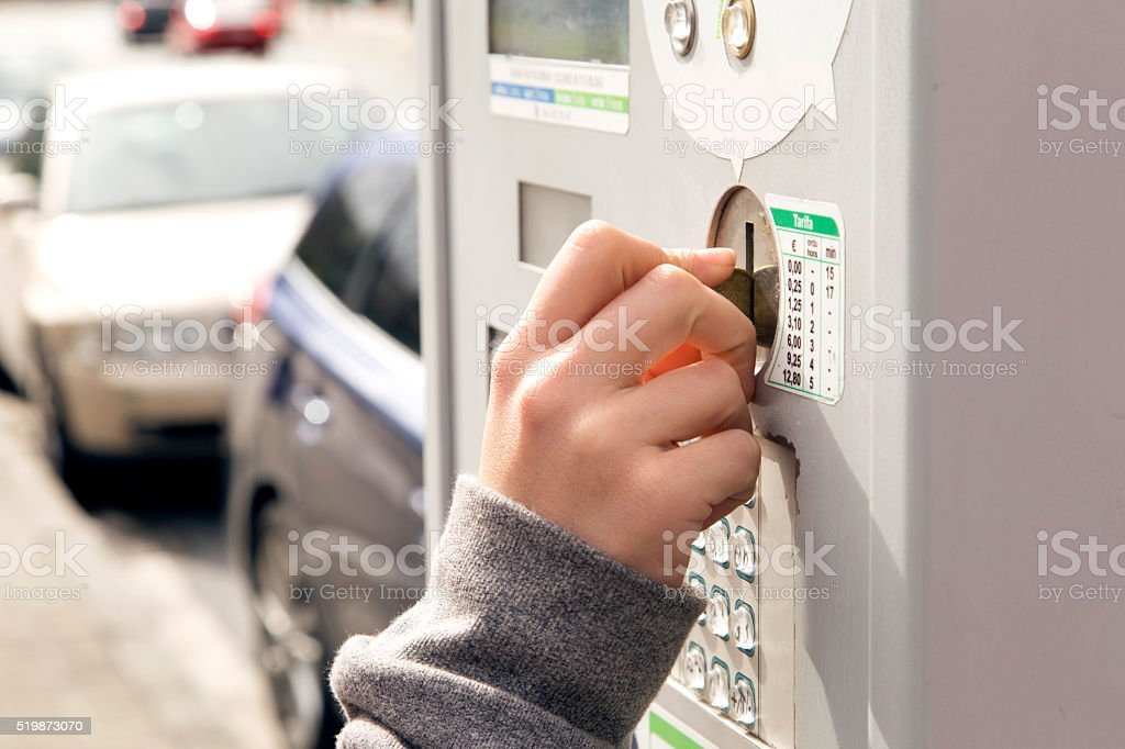 One human hand inserting a coin in a parking meter. stock photo