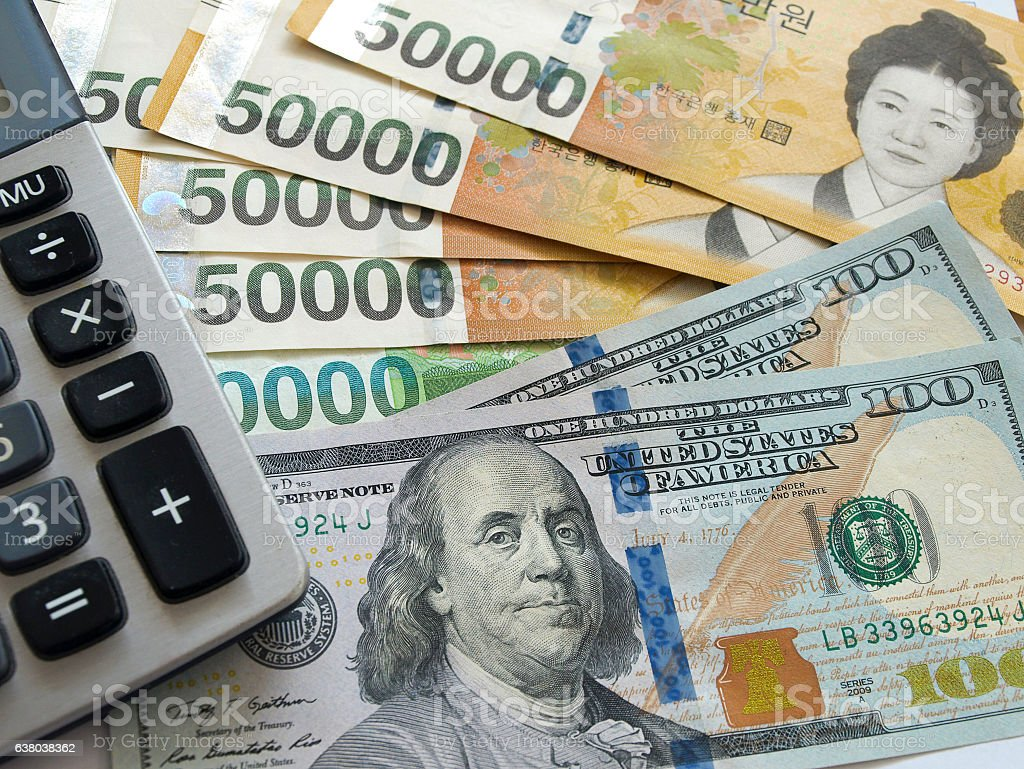 US one hundred dollar and Korean banknotes with calculator stock photo