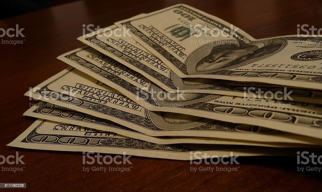 One hundred dollar banknotes funned out on table stock photo
