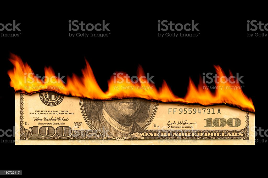 One hundred dollar bill on fire on black background stock photo