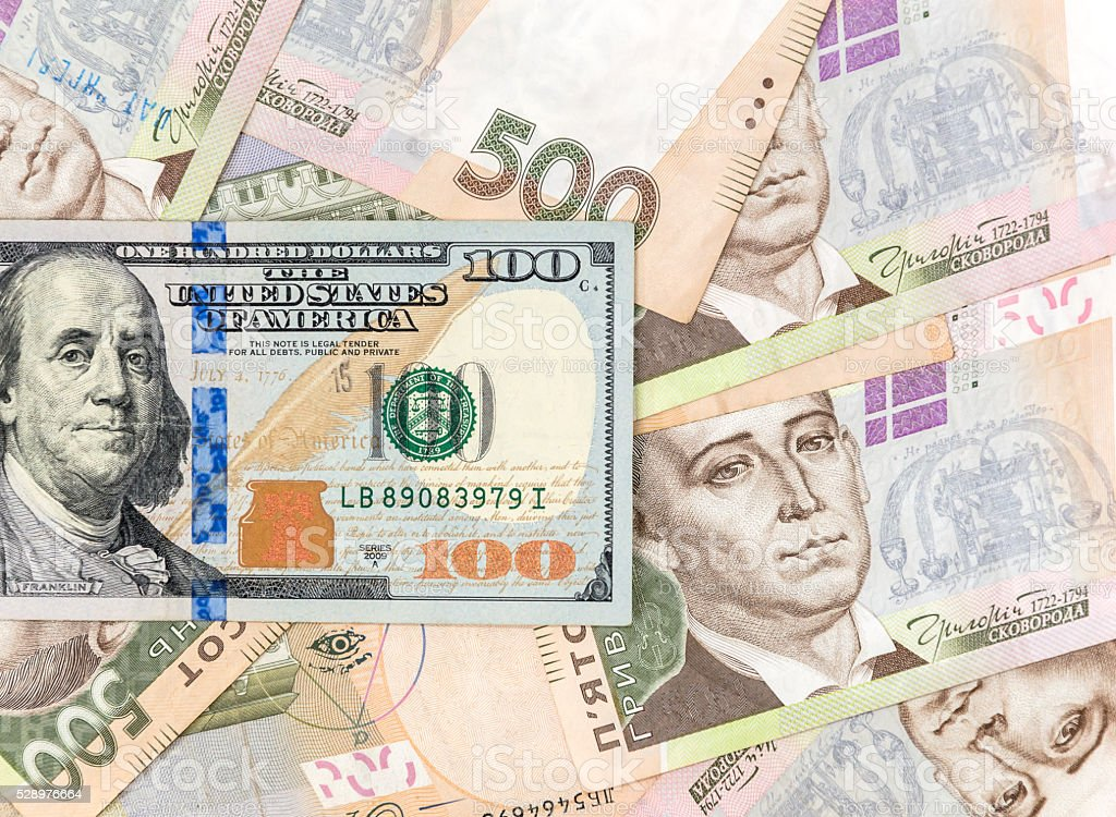 One hundred dollar bill on the background of ukrainian hryvnia stock photo