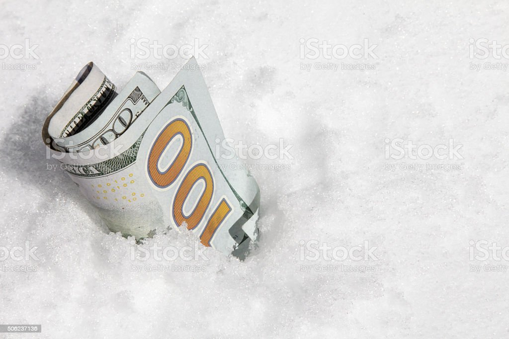 One hundred dollar bill partially buried in snow stock photo