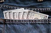 One hundred dollar bills in jeans hip pocket