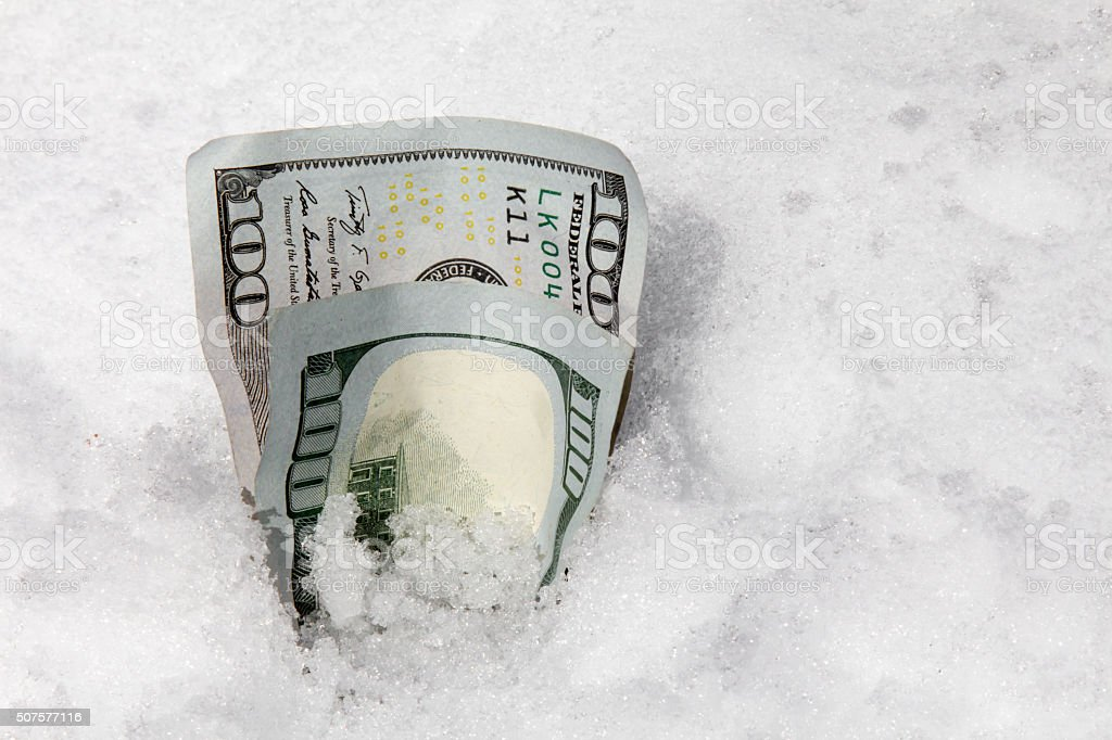 One hundred dollar bills in the snow stock photo