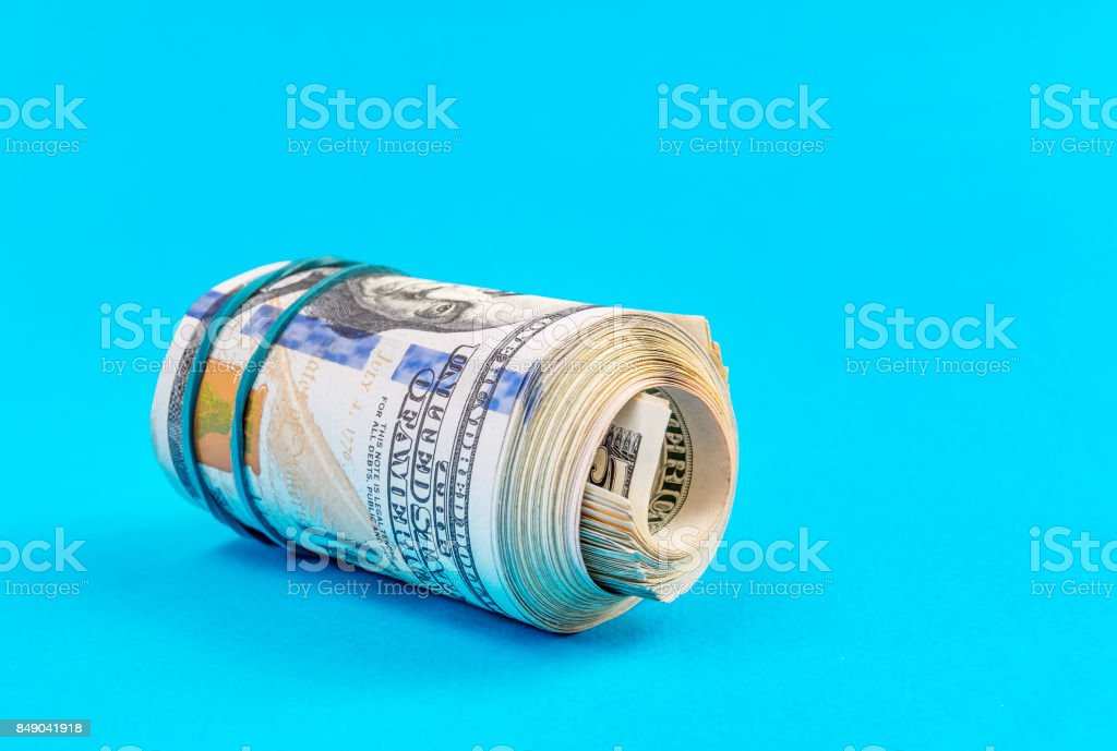 US one hundred dollar bills rolled up with rubber band on a blue. stock photo