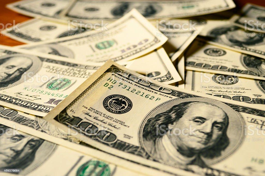 One hundred dollar bills spread across table stock photo