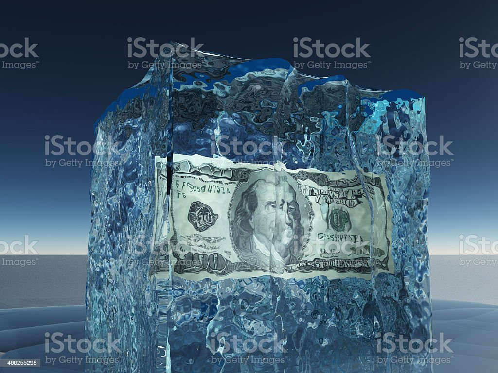 A one hundred dollar paper bill in the middle of a ice cube stock photo