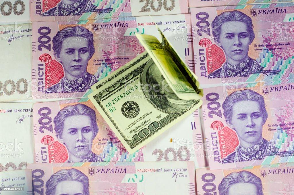 One hundred dollars banknotes on the background of ukrainian hryvnas stock photo