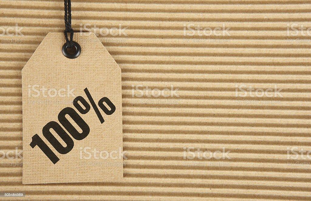 100% on cardboard tag on corrugated cardboard background.