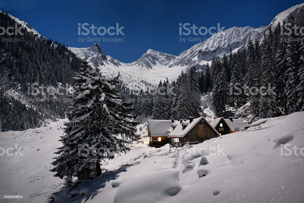One hut in the mountains on a winter night stock photo