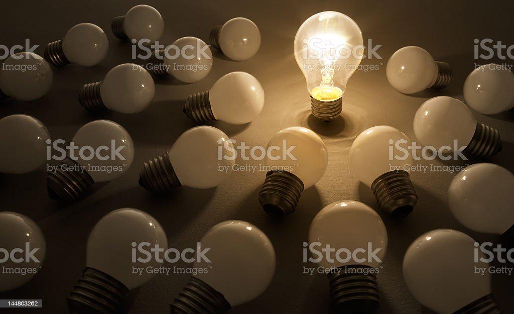 One illuminated lightbulb with many dim lightbulbs around stock photo