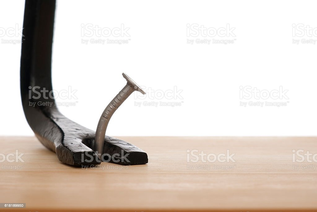 One iron nail and scrap on a wooden board stock photo