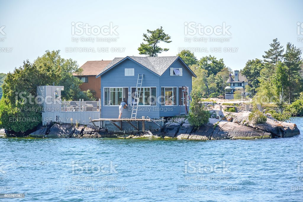 One Island with the blue house in Thousand Islands stock photo