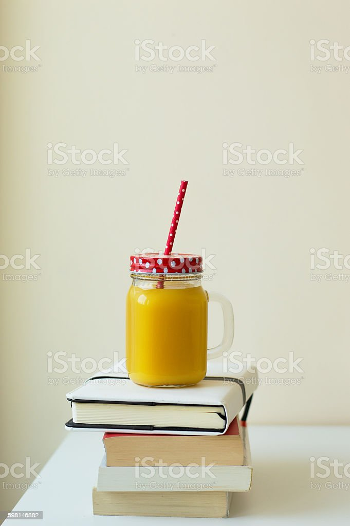 One jar with orange juice on the pile of books stock photo