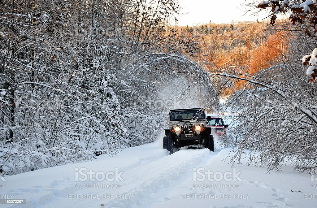 One Jeep Tows Out Another Stuck in Snow stock photo