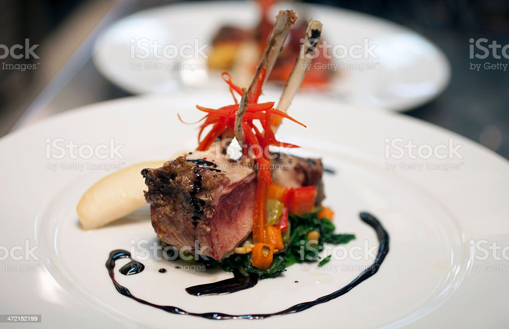 One lamb chop placed on veggies with a swirl of dark liquid  stock photo