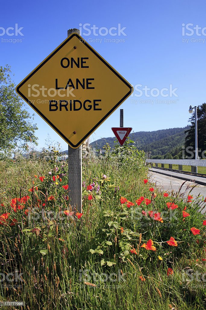 One lane bridge on country road with poppies stock photo
