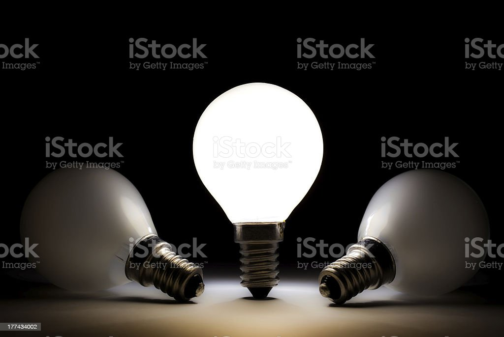 One light bulb shining in a dark space stock photo