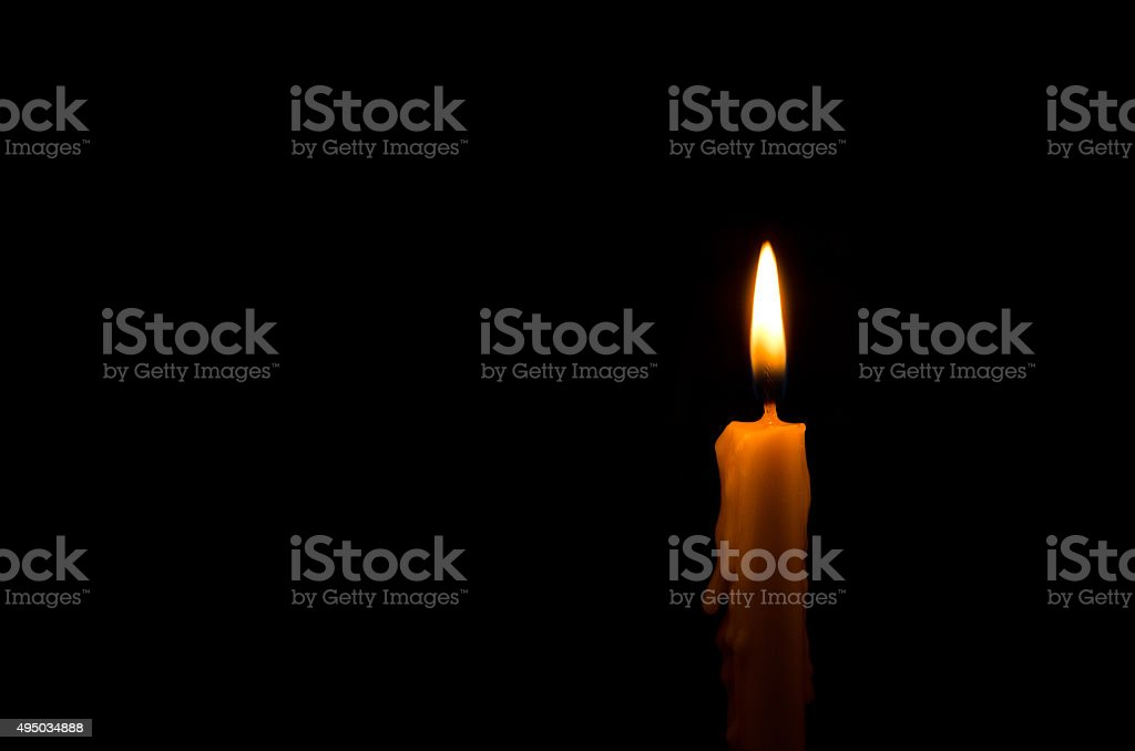 One light candle burning brightly in the black background stock photo