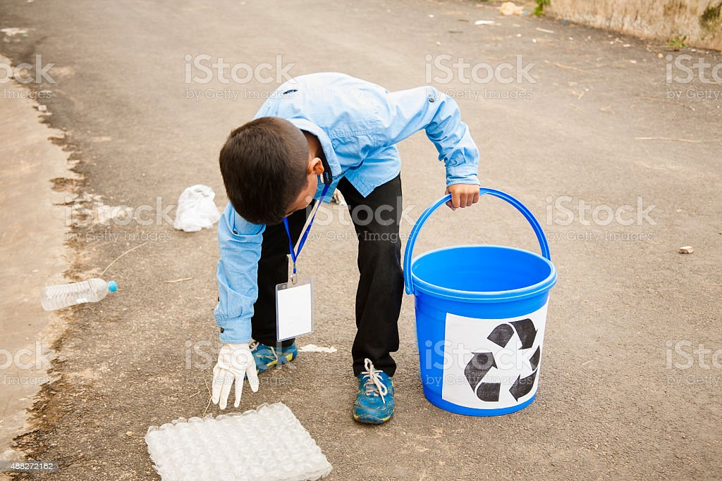 One little boy picking up trash to recycle. Roadside setting. stock photo