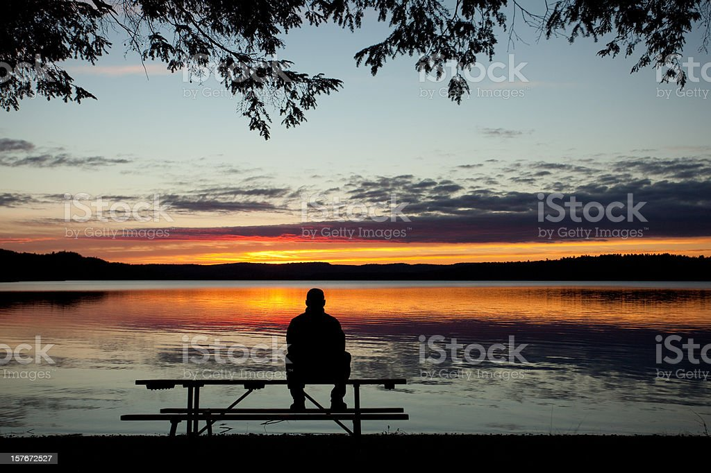 One Lonely Man Watching the Sunset Over Lake royalty-free stock photo