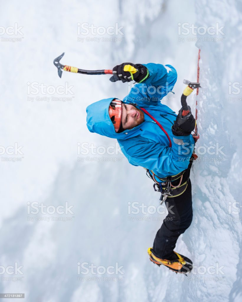 One Male Ice climber climbing  frozen cascade stock photo