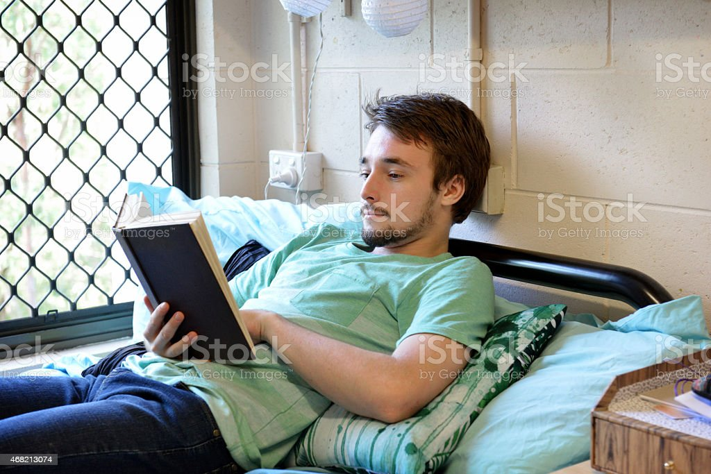 One male student laying and reading a book stock photo
