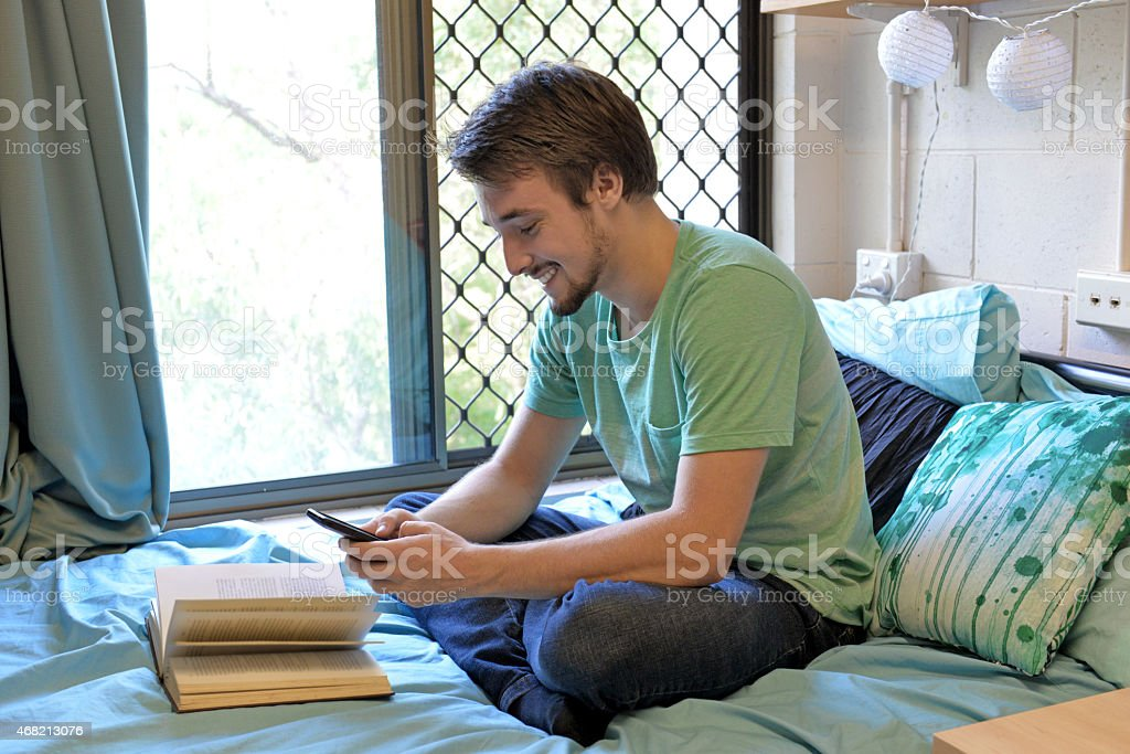 One male student sitting on a bed texting stock photo