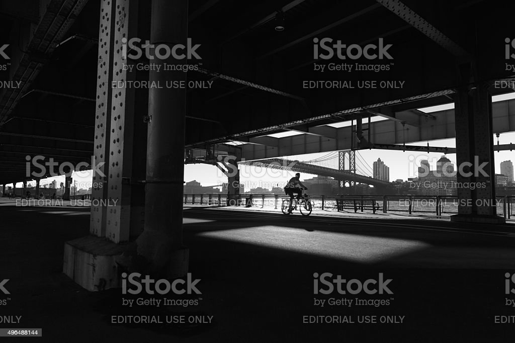 One Man cycles in shadows under the Manhattan Bridge NYC stock photo