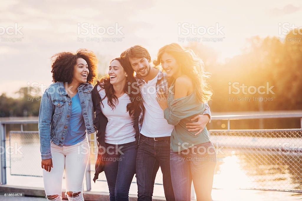 One man holding three women outdoors at sunset stock photo