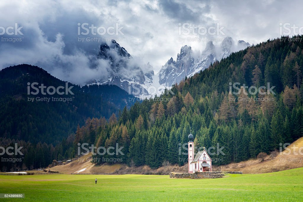 One Man in front of  San Giovanni Church & Dolomites stock photo
