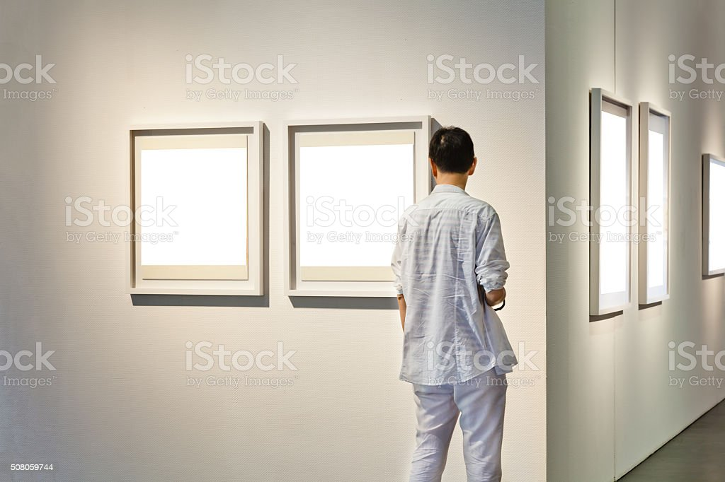 One man looking at white frames in an art gallery stock photo