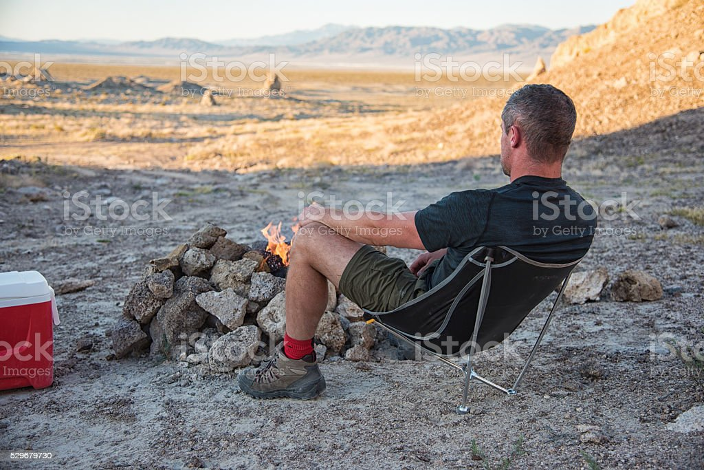 One Man Relaxing at the Campfire Looking at the View stock photo