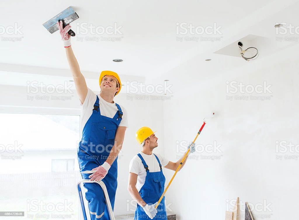 One man repairing ceiling and one painting wall of room stock photo