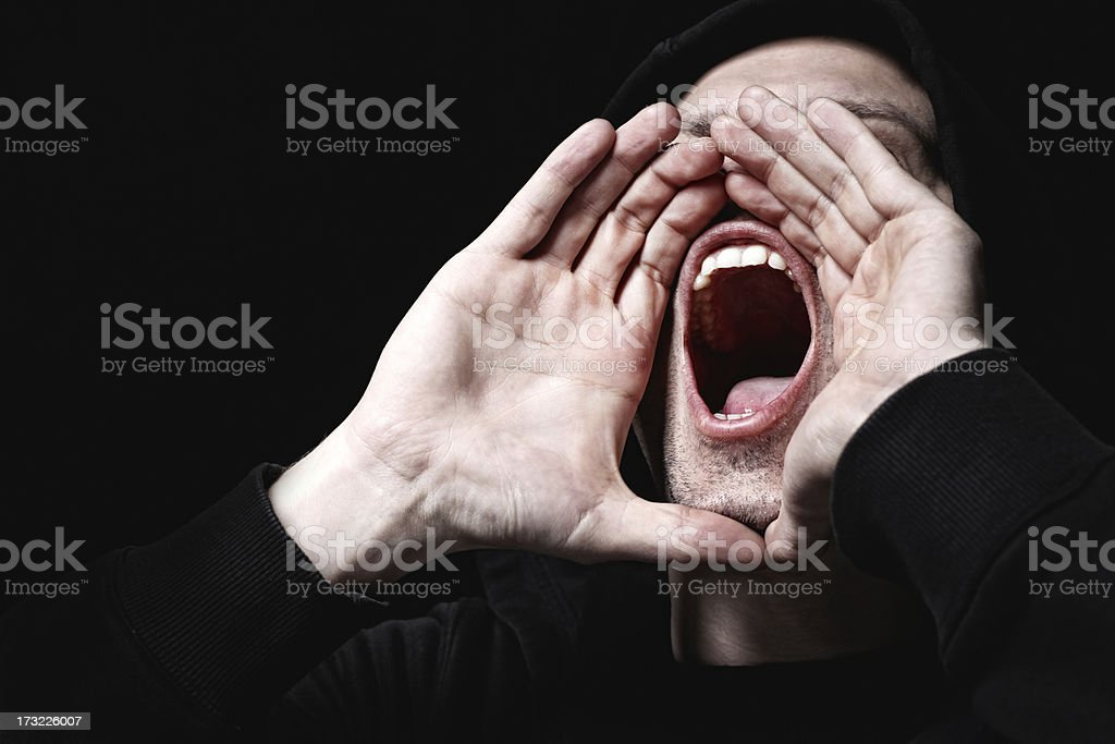 One man shouting loudly in the air against a plain backdrop royalty-free stock photo