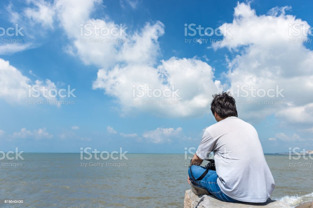 One man sitting alone, looking white cloud on the sky and thinking stock photo