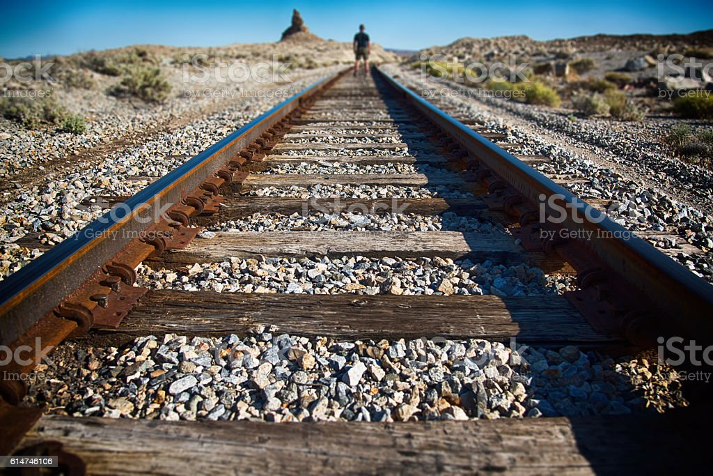One Man Standing On The Railroad Tracks stock photo