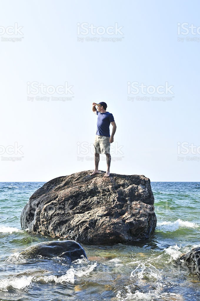 One man stranded on a large rock in the ocean royalty-free stock photo