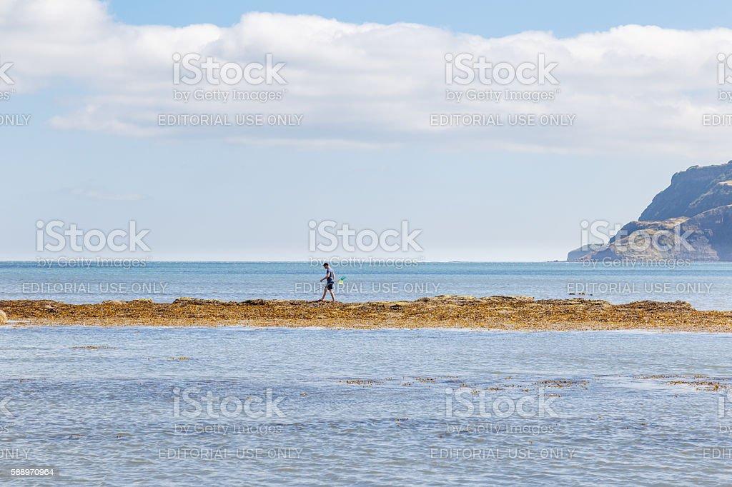 One man walking out on sandbank with fishing net stock photo