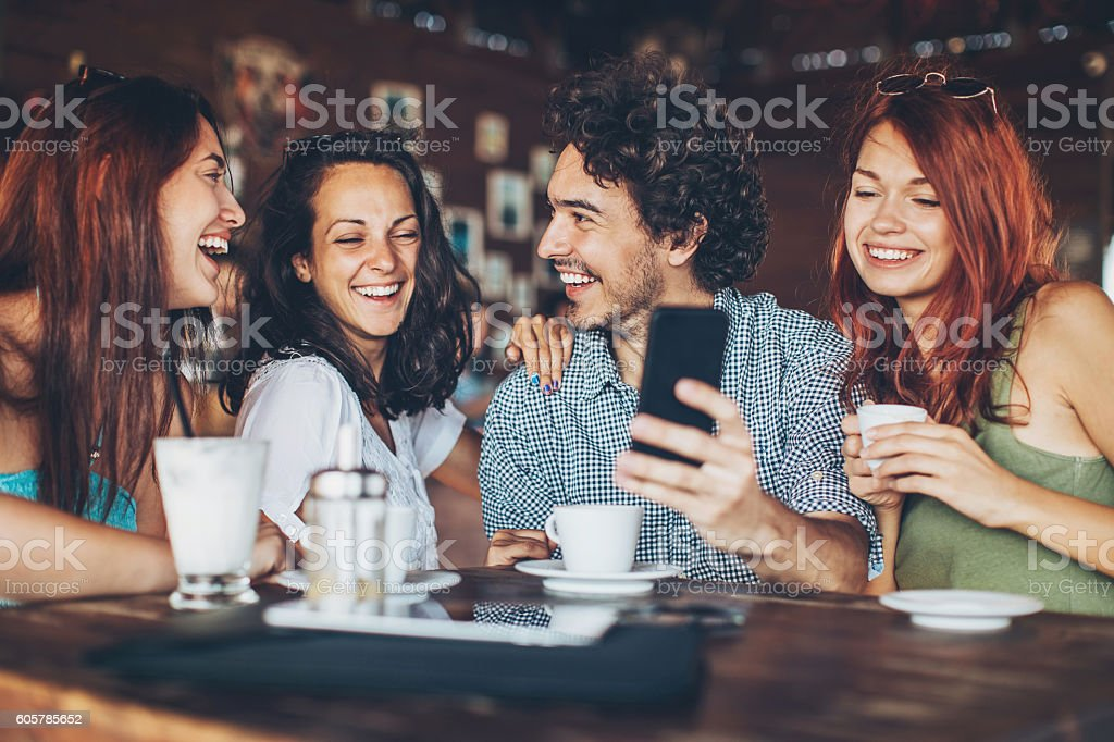 One man with three women in cafe stock photo